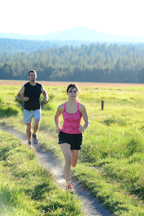Couple running, near Dillon Falls, Deschutes River, Bend,Oregon,USA.model release 0238,