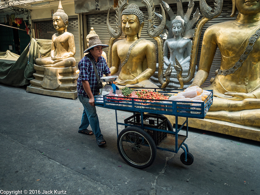 09 MARCH 2016 - BANGKOK, THAILAND:  A fruit vendor pushes his cart of berries past statues of the Buddha for sale near Thanon Bamrung Muang in Bangkok. The street is lined with workshops that make statues of the Buddha and revered Thai Buddhist monks. Once located just outside Bangkok's city walls, it's now in the heart of the city.     PHOTO BY JACK KURTZ