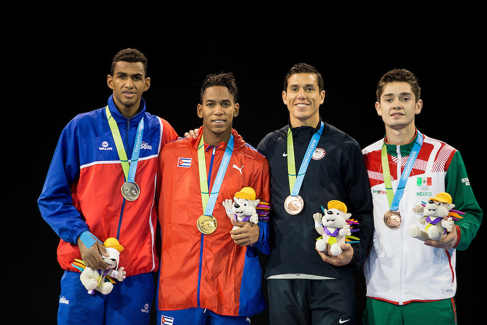 Medalists in the men's taekwondo -80 kg division, from left, silver medalist Moises Hernandez of the Dominican Republic, gold medalist Jose Cobas of Cuba, and bronze medalists Steven Lopez of the United States and Rene Lizarraga of Mexico pose for photos during the medal ceremonies at the 2015 Pan American Games in Toronto, Canada, July 21,  2015.  AFP PHOTO/GEOFF ROBINS