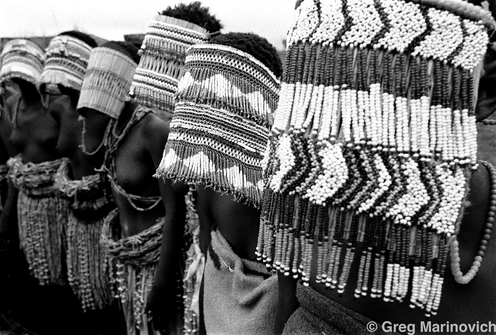 Masked BaSotho female initiates - bale - in their teens, sing outside their seclusion hut in the former QwaQwa homeland, Free State, South Africa, Dec 22, 1999.  The girls are undergoing a ritual of puberty that will allow them to get married.  The different masks are all related to identities that the girls have within the initiation school. (Greg Marinovich)