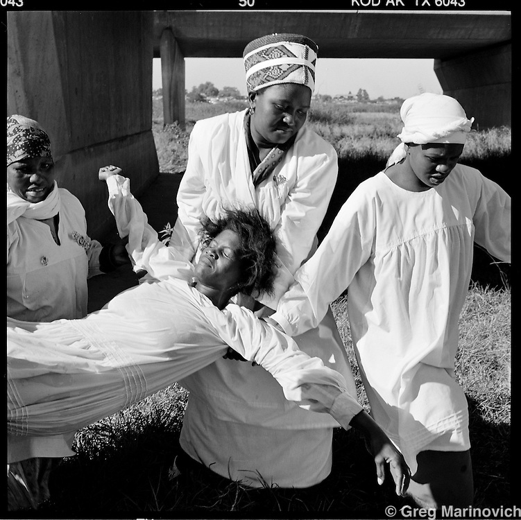 A woman who was felled by the spirit during her baptism in the Klip River in Soweto 1999.  The founder Isaiah Shembe is seen as a spiritual descendent of Moses and Jesus, and th church embraces traditional Zulu values and customs. Photo Greg Marinovich