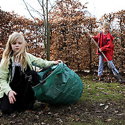 "Rumlepotten Collective, Aarhus, Denmark, March, 27th, 2010. Community's members participate in ""working day"", to help in cleaning, maintenance, renovation of the common house. Children collecting dried leaves."