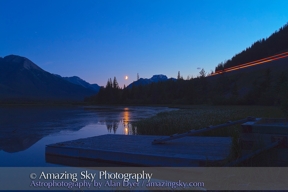 The waxing crescent Moon over Vermilion Lakes, Banff, Alberta, on August 4, 2011. This is an HDR stack of 5 exposures at 2/3rds stop intervals to capture the dark foreground detail and the bright Moon on one image. Lights from passing traffic on Highway 1 above the lakes produced the streak at right.