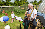 20140601 Free for editorial use image<br /> <br /> Halifax colleagues in Bournemouth are proud to give extra back to their local community by hosting their Big Lunch event on Sunday 01 June 2014.<br /> <br /> Halifax Branch Manager David Farmer plays guitar during The Big Lunch at the New Leaf Allotment in Bournemouth. <br /> <br /> For more information please contact: Catherine Eastham on 020 3697 4304<br /> <br /> If you require a higher resolution image or you have any other onEdition photographic enquiries, please contact onEdition on 0845 900 2 900 or email info@onEdition.com<br /> This image is copyright the onEdition 2014&copy;.<br /> This image has been supplied by onEdition and must be credited onEdition. The author is asserting his full Moral rights in relation to the publication of this image. Rights for onward transmission of any image or file is not granted or implied. Changing or deleting Copyright information is illegal as specified in the Copyright, Design and Patents Act 1988. If you are in any way unsure of your right to publish this image please contact onEdition on 0845 900 2 900 or email info@onEdition.com