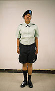 U.S. Army Private Yavonne Ortiz stands next to a wall with half of her dress uniform and half of physical training uniform on during basic military training at Fort Jackson, S.C., on October 23, 2008.