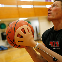 Bob Radocy of TRS Inc. holds a basketball with a prosthetic hand designed for the sport at a gym in Boulder, Colorado August 21, 2009. Radocy designs and builds prosthetic attachments that allow amputee athletes to participate in multiple sports.  REUTERS/Rick Wilking (UNITED STATES)