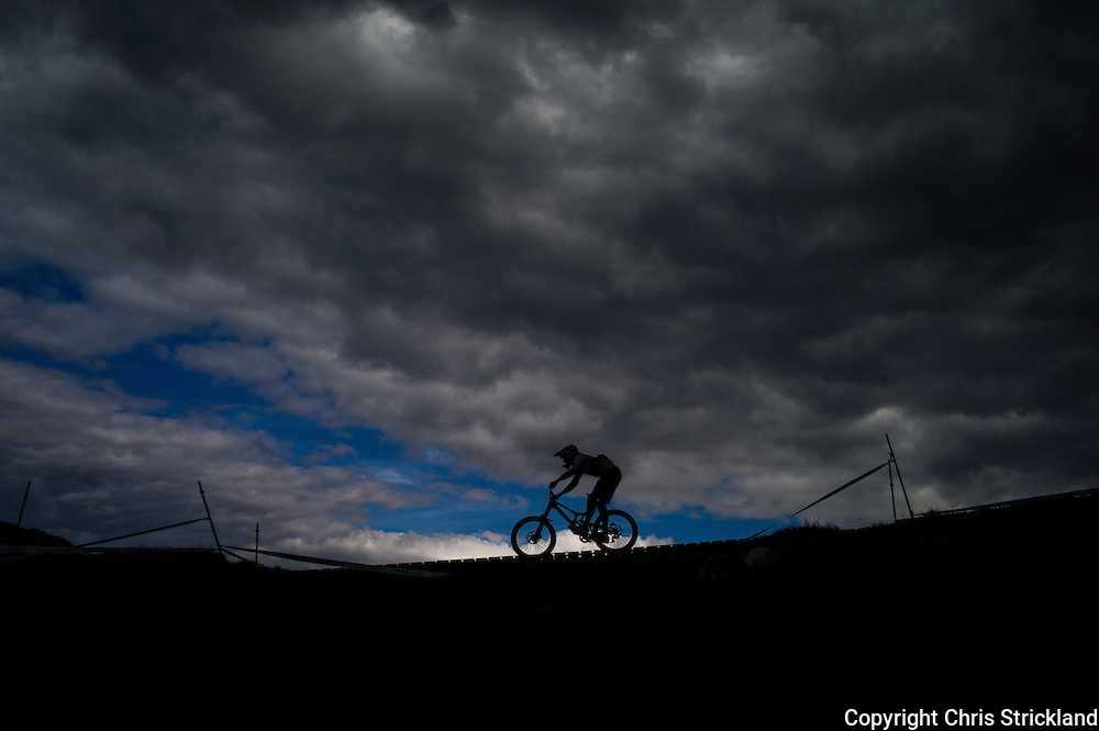 Nevis Range, Fort William, Scotland, UK, 9th June 2013. A rider is silhouetted on the ridge of Nevis Range during the Mens Elite Final in the UCI Mountain Bike World Cup.
