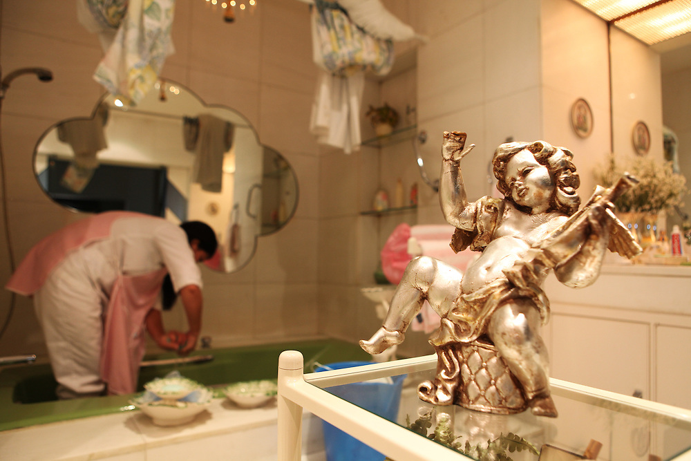 A Filipino domestic worker cleans her employers' bathtub.