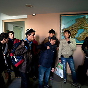 Illegal immigrants from Afghanistan are brought in for processing at the main Police headquarters in Mytilene, Lesvos.  Image © Angelos Giotopoulos/Falcon Photo Agency..