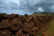 A wall made of red lava stretches towards the Rano Raraku volcano in Easter Island