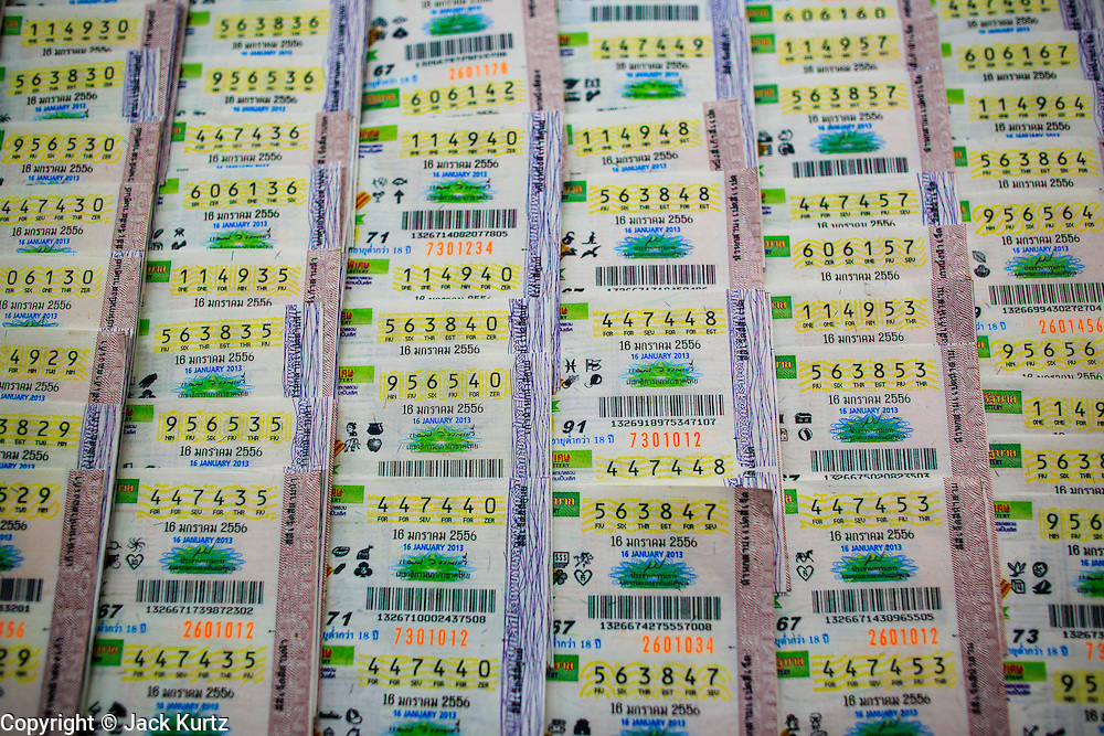 04 JANUARY 2012 - BANGKOK, THAILAND: Lottery tickets for sale on Sukhumvit Soi 77 in Bangkok. About 20 million Thais, nearly ? of the country's 65 million people, play lottery type games. The lotteries were brought to Thailand two hundred years ago by Chinese immigrants. Lottery agents are usually friends who collect bets but do not ask for money before the drawing. The lottery shops are close to Wat Mahabut and many people go the temple to see the fortune tellers and pray at the shrines there for guidance on the numbers to play in the lottery games.    PHOTO BY JACK KURTZ