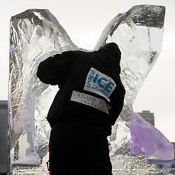 London, UK - 11 January 2012: a sculpture carves a block of ice during the Ice sculpting festival 2013 in Canary Warf.