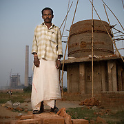 Anand Oram (34) in front of the half constructed temple at the resettlement colony at Jharsuguda. He is the priest of this temple and the son of the priest of the original village.