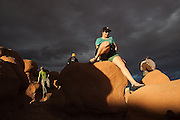 Katy Barnhart climbs off a boulder, at sunset, during a geology field trip to Goblin Valley State Park, Utah.