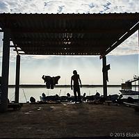 Trabajador despertando al amanecer en el muelle de Santa Rosalía para iniciar su jornada como cargador.