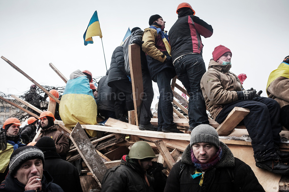 Anti-government protesters stand guard at one of the barricades defending Maidan Square against police and government supporters on December 9, 2013 in Kiev, Ukraine. Thousands of people have been protesting against the government since a decision by Ukrainian president Viktor Yanukovych to suspend a trade and partnership agreement with the European Union in favor of incentives from Russia was made recently.